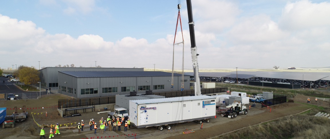 Large crane holds up a data center module for transport into place on campus, with a construction crew gathered behind the module.