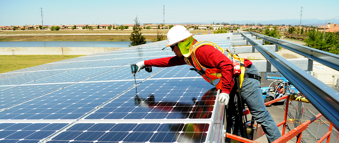 Cupertino Electric electrician installs solar PV panels to complete a parking lot canopy system
