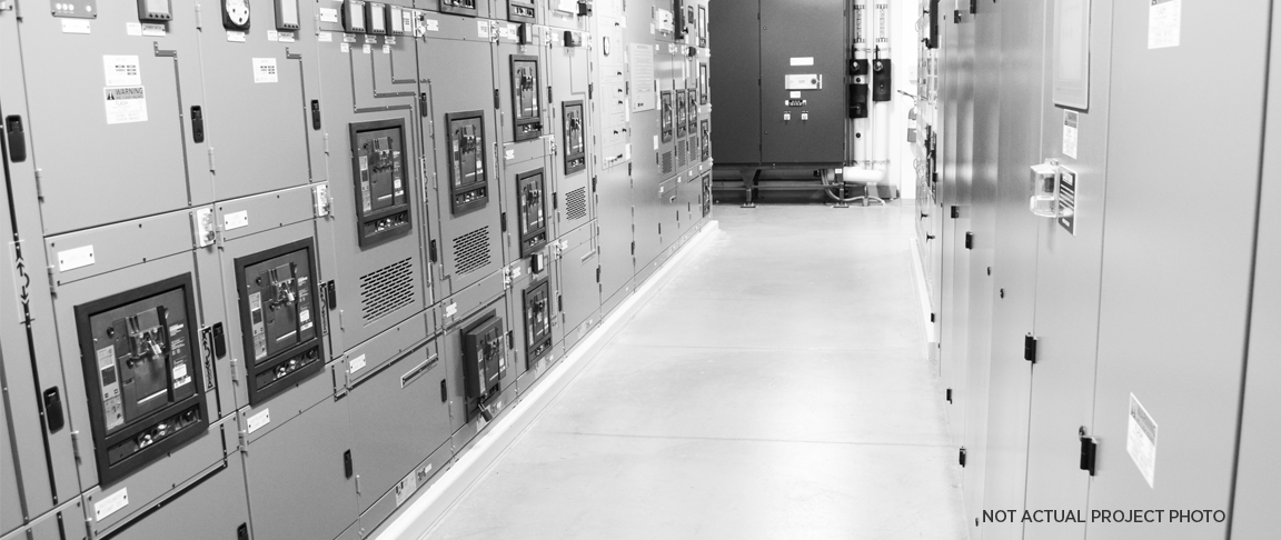 Black and white photo of electrical room showing many switches, lights and buttons.