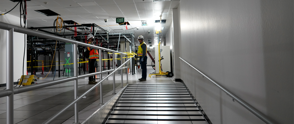 Two men with construction personal protective gear (vests, hard hats, etc.) standing in a partially demolished data center hall with racks missing